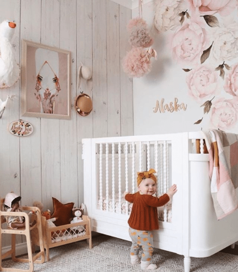 nursery using Whitewashed Timber wallpaper, the best seller for 2017, with white crib. wood carved name Alaska and baby girl standing