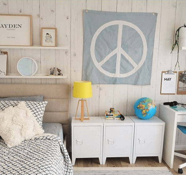 Teenagers bedroom with Whitewashed Timber wallpaper, the best seller for 2017, hung vertically with a peace sign on the wall