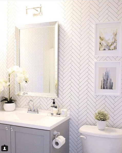 a bright white bathroom. The sink has gray wooden doors with a white top. A mirror with silver trim sits above the sink. On the wall is Tile Progress Wallpaper by Milton & King with two framed pictures of cactus.