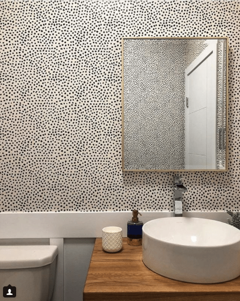 a powder room with light wood cabinetry. On top is a white sink bowl. Leo's Spots wallpaper manufactured by Milton & King and designed by Jillian Harris is on the wall and in the mirror reflecting the opposite wall.