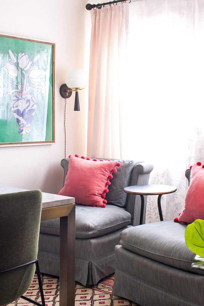 two vintage gray slip chairs with salmon colour pillows with a picture on the left wall of a blue and white vase with flowers against a green background