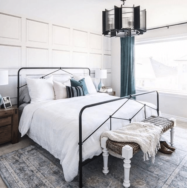 bedroom in the basement with white The Parlour Wallpaper on the wall behind the bed. The bed has white linen and there is a large soft rug on the floor with blue grey tones
