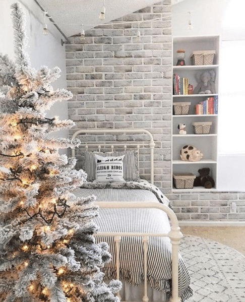 girl's bedroom with limewashed brick wallpaper behind the bed and a frost covered fake tree at the foot of the bed.