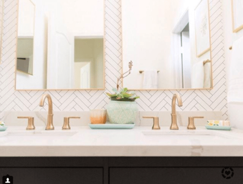 Image of final remodeled guest bathroom. it has a black painted vanity, white marble countertop with brass faucet and handles at a his and hers sink and Tile Progress Wallpaper against the back wall from Milton & King