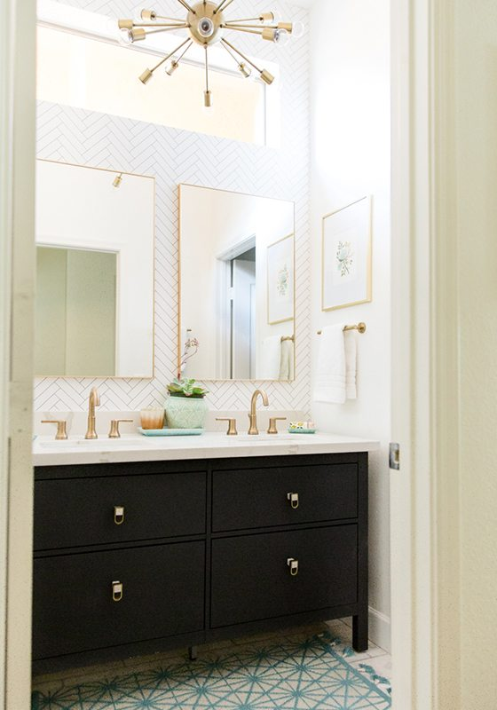 photo of a bathroom with dark cabinets, a his and hers sink with brass faucets and handles and a herringbone wallpaper called Tile Progress from Milton & King
