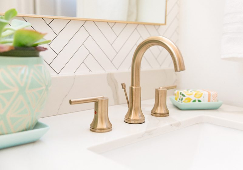 Close up photo of the brass plated faucets in the bathroom with Tile Progress Wallpaper from Milton & King in the background