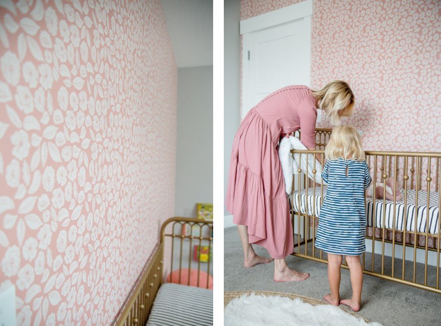 Nursery by The Simple Sweet Life with pink wallpaper called Baby Bloom from Milton & King with a gold painted crib and mother and daughter watching the baby