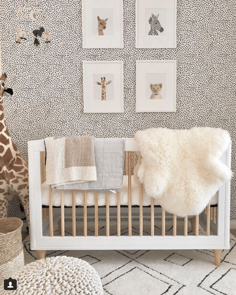 a nursery with animals themes. The crib has a white frame with maple wood dowels. hanging over the crib is a white fur blanket and two light colored towels. On the wall behind the crib is Leo's Spots wallpaper designed by Jillian Harris and manufactured by Milton & King. On the wallpapered wall are four framed pictures of a llama, zebra, giraffe and lion. To the left of the crib is a large stuffed giraffe toy. The floor has a large off-white soft rug with diamond shaped patterns in black outlines. Towards the front of the photo to the bottom left is a crocheted stool and wicker basket