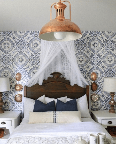 bedroom with blue Heritage Tiles Wallpaper by Milton & King on the wall behind a queen sized bed, two white end tables, each with a small lamp and a big bronze ceiling lamp