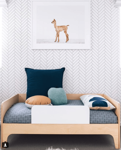 toddlers bedroom with Tile Progress wallpaper on the wall with a framed picture of a baby deer. Bed bed has a light wood bedframe and blue pattern bedding