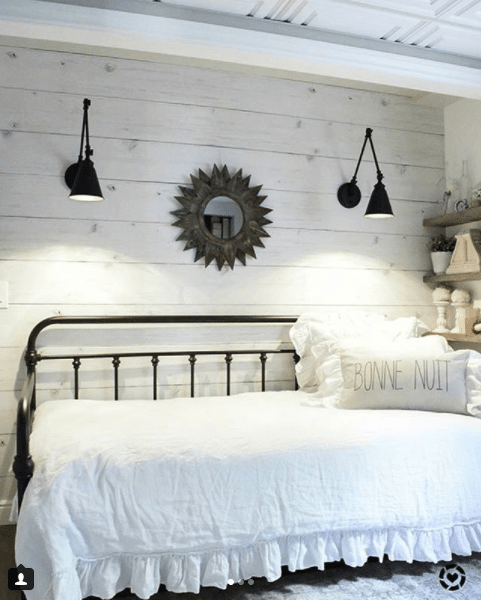"""guest room with Whitewashed Timber wallpaper on the wall with a white daybed and black railing. Two black sconces hang above the bed. A pillow says """"bonne nuit"""""""