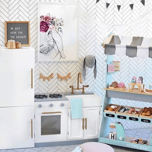 Kids playroom with Kmart kitchen set and white Tile Progress Wallpaper from Milton & King on the wall