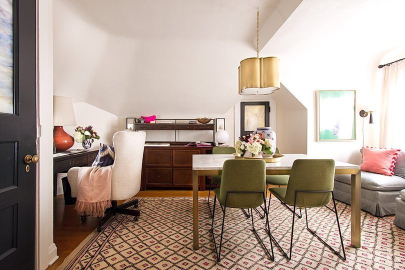 a wide photo of Nicole Balch's home office. On the left is her computer desk with a white upholstered chair. In the center of the room is a table with a floral arrangement on top with 4 olive green chairs. On the let is a gray sofa with pink pillows
