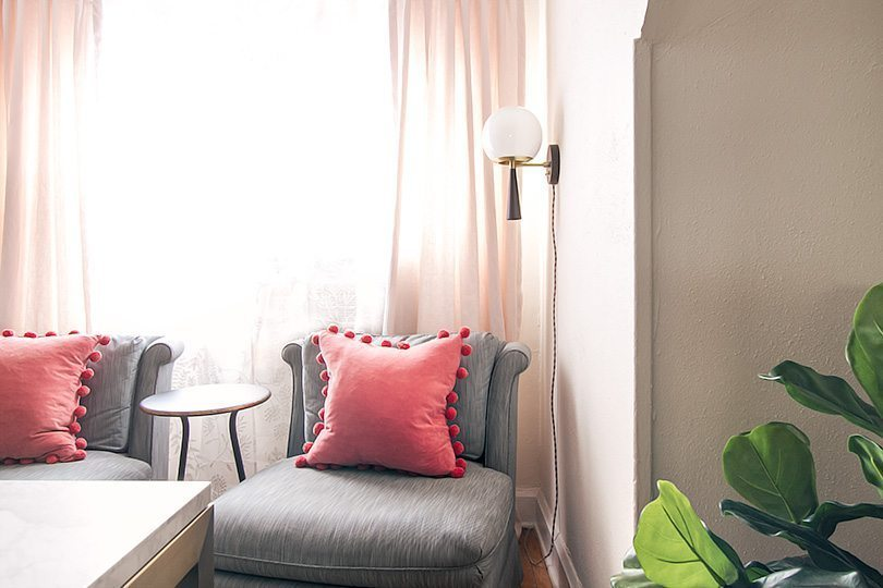 gray vintage slipper chairs with a salmon colored pillow. on the right is a large leafed plant