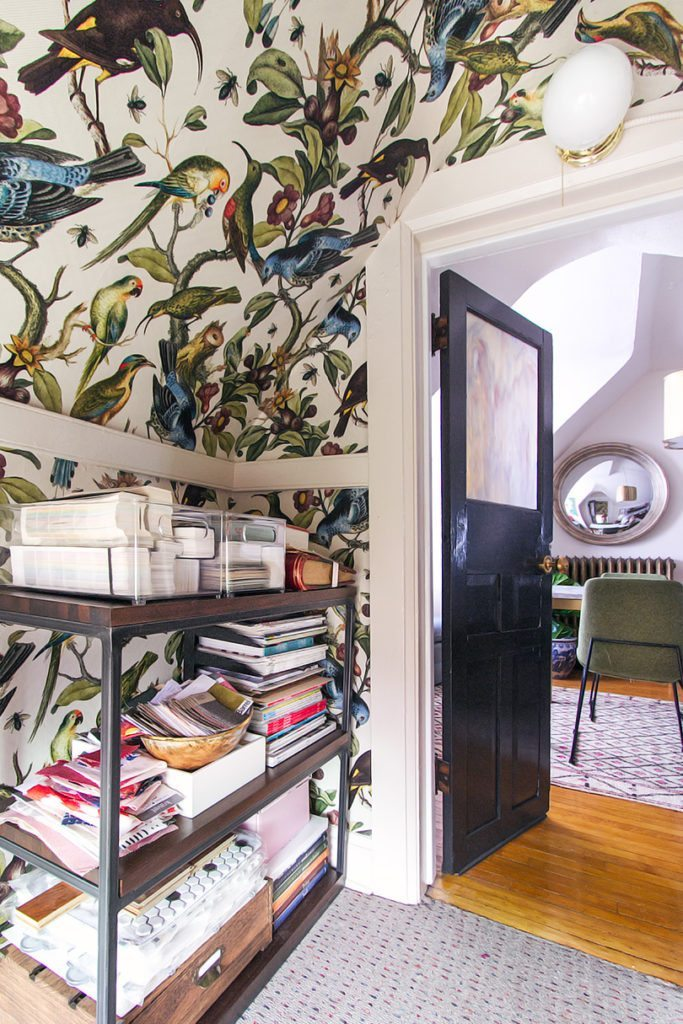 Pictured is a view out of the closet. On the left wall and ceiling is the Orinthology wallpaper by Milton & King. In front of the wall is walnut shelving with stacks of magazines, books and fabrics. There is a dark wood opened door leading into the office.