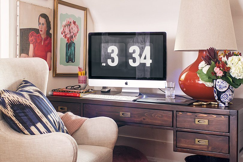 photo showing the time 3:34PM on the computer monitor that sits on a dark wooden desk. On the right of the desk is an orange lamp with a floral arrangement. To the left are two photos on the wall and in front of the desk is a white chair with a blue and white patterned pillow