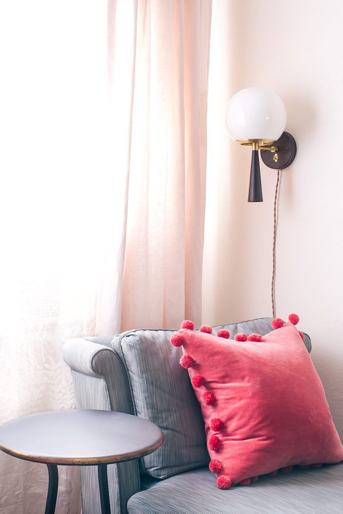 gray vintage slip chairs with salmon colored pillow and wall sconce