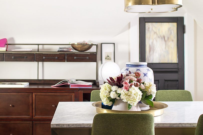 a shot of the table in the middle of the office with a flower arrangement in the center. Behind the table you can see a closed dark door and to the left, a brown shelving unit
