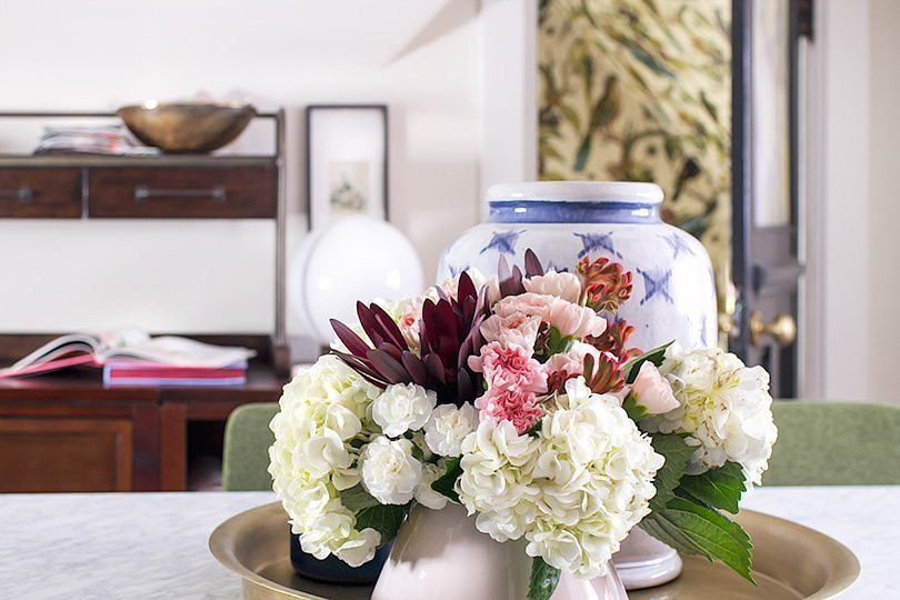 floral arrangement of white, pink and red flowers on top of marble topped dining table. In the background is a blurry image of an opened door with Orinthology wallpaper from Milton & King peeking through