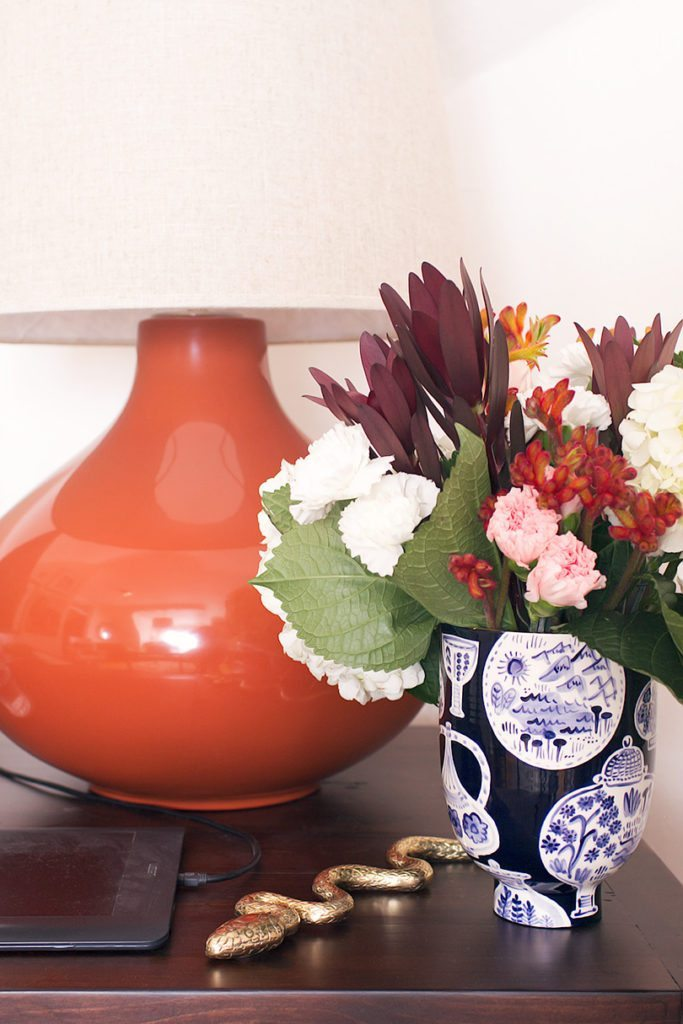 a close up shot of the orange ceramic lamp on the right side of the desk. A flat brass ornamental snake sits next to a black vase with blue print on it and a small arrangement of colorful flowers.