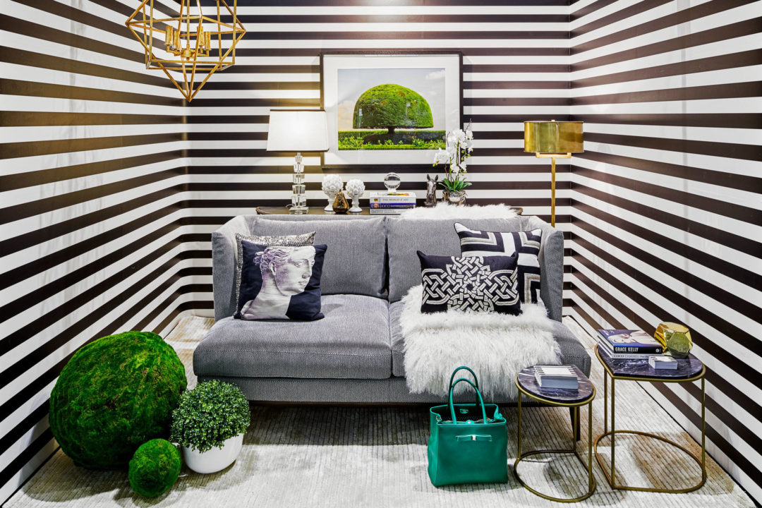 Sitting room with grey loveseat and horizontal black and white striped wallpaper