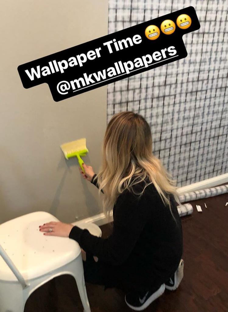woman applying paste to the wall to hang Earth Grey Brick Wallpaper by Milton & King